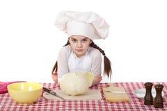 Το πορτρέτο ενός μικρού κοριτσιού σε μια άσπρη ποδιά και το καπέλο αρχιμαγείρων τεμαχίζουν το γ Στοκ φωτογραφίες με δικαίωμα ελεύθερης χρήσης