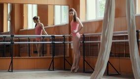 Το πορτρέτο ενός νέου κοριτσιού εκτελεί χαριτωμένα τα τεχνάσματα acrobatics στο στούντιο Στοκ εικόνα με δικαίωμα ελεύθερης χρήσης