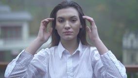 Το πορτρέτο ενός νέου κοριτσιού με το μακρύ μαύρο καλό κορίτσι τρίχας ισιώνει τις συγκινήσεις τρίχας της στο πρόσωπο ενός όμορφου απόθεμα βίντεο