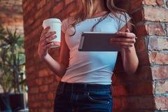 Το πορτρέτο ενός νέου ξανθού θηλυκού κρατά ένα φλυτζάνι ενός take-$l*away καφέ και της χρησιμοποίησης μιας ψηφιακής ταμπλέτας κλί Στοκ εικόνα με δικαίωμα ελεύθερης χρήσης