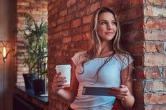 Το πορτρέτο ενός νέου ξανθού θηλυκού κρατά ένα φλυτζάνι ενός take-$l*away καφέ και μιας ψηφιακής ταμπλέτας κλίνοντας ενάντια σε έ Στοκ εικόνες με δικαίωμα ελεύθερης χρήσης