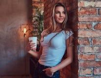 Το πορτρέτο ενός νέου ξανθού θηλυκού κρατά ένα φλυτζάνι ενός take-$l*away καφέ κλίνοντας ενάντια σε έναν τουβλότοιχο σε ένα δωμάτ Στοκ Φωτογραφία