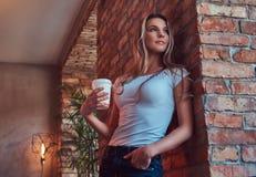 Το πορτρέτο ενός νέου ξανθού θηλυκού κρατά ένα φλυτζάνι ενός take-$l*away καφέ κλίνοντας ενάντια σε έναν τουβλότοιχο σε ένα δωμάτ Στοκ Εικόνα