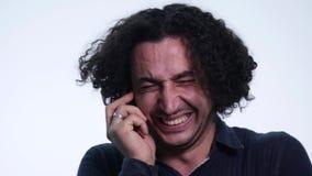 Το πορτρέτο ενός νέου όμορφου ατόμου μιλά στο τηλέφωνο και το γέλιο στο άσπρο υπόβαθρο φιλμ μικρού μήκους