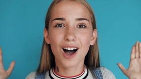 Το πορτρέτο ενός νέου όμορφου καυκάσιου κοριτσιού στην μπλούζα κραυγάζει wow στην έκπληξη στο μπλε υπόβαθρο Συγκλονισμένος hipste φιλμ μικρού μήκους