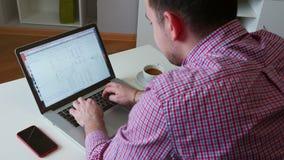 Το πορτρέτο ενός νεαρού άνδρα, ενός προγραμματιστή ή ενός εμπόρου, εξετάζει τα διαγράμματα στην ανταλλαγή, στο σπίτι με το lap-to φιλμ μικρού μήκους