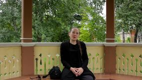 Το πορτρέτο ενός χαμογελώντας κοριτσιού με την πλεξούδα έντυσε στη μαύρη συνεδρίαση στο gazebo απόθεμα βίντεο