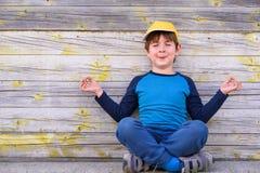 Το πορτρέτο ενός χαριτωμένου εύθυμου αγοριού με την κίτρινη συνεδρίαση ΚΑΠ υπαίθρια στη γιόγκα θέτει Στοκ Εικόνες