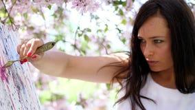 Το πορτρέτο ενός όμορφου ζωγράφου γυναικών στο άσπρο φόρεμα, καλλιτέχνης χρωματίζει μια εικόνα των λουλουδιών στο ανθίζοντας μήλο απόθεμα βίντεο