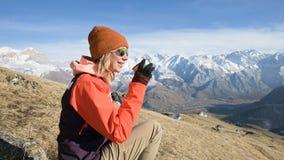 Το πορτρέτο ενός όμορφου κοριτσιού σε ένα καπέλο και τα γυαλιά ηλίου με μια κούπα στα χέρια της πίνει τον καφέ ή το τσάι καθμένος απόθεμα βίντεο