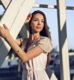 Το πορτρέτο ενός όμορφου κοριτσιού στο φόρεμα που στέκεται στους ξύλινους στυλοβάτες, που στηρίζεται μετά από την εργασία, διαμορ Στοκ εικόνες με δικαίωμα ελεύθερης χρήσης