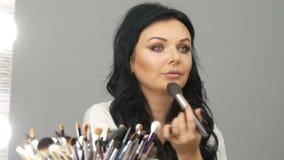 Το πορτρέτο ενός όμορφου μπλε-eyed προτύπου γυναικών με τη μακροχρόνια μαύρη συνεδρίαση τρίχας μπροστά από τον καθρέφτη και ρυθμί φιλμ μικρού μήκους