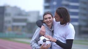 Το πορτρέτο ενός όμορφου νέου ζεύγους sportswear υπαίθρια στον όμορφο τύπο sportswear φιλά τη φίλη του απόθεμα βίντεο
