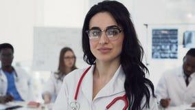 Το πορτρέτο ενός όμορφου νέου θηλυκού γιατρού στα γυαλιά εξετάζει τη κάμερα, χαμογελώντας ενώ οι συνάδελφοί της έχουν απόθεμα βίντεο
