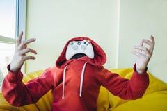 Το πορτρέτο ενός gamer είναι αντ' αυτού πρόσωπο ένα πηδάλιο για τα τηλεοπτικά παιχνίδια Η έννοια των τηλεοπτικών παιχνιδιών Στοκ εικόνες με δικαίωμα ελεύθερης χρήσης