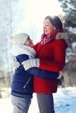 Το πορτρέτο ζωής της ευτυχούς οικογένειας, γιος αγκαλιάζει τη μητέρα του το χειμώνα στοκ φωτογραφία