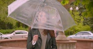 Το πορτρέτο καυκάσιο θηλυκό rocker brunette ανοίγει την ομπρέλα προβλέποντας τη βροχή στο πράσινο βροχερό πάρκο απόθεμα βίντεο