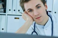 Το πορτρέτο κινηματογραφήσεων σε πρώτο πλάνο ενός νέου αρσενικού γιατρού, το κεφάλι του από το χέρι που λειτουργεί στον υπολογιστ Στοκ Εικόνες