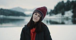 Το πορτρέτο κινηματογραφήσεων σε πρώτο πλάνο μιας νέας κυρίας εκτός από μια μεγάλη λίμνη και ένα χιονώδες βουνό που φαίνονται ευθ απόθεμα βίντεο