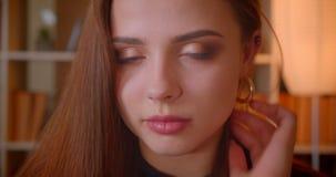 Το πορτρέτο κινηματογραφήσεων σε πρώτο πλάνο της νέας γυναίκας σπουδαστή χαμογελά στη κάμερα που είναι μέτρια και ντροπαλή στο υπ φιλμ μικρού μήκους