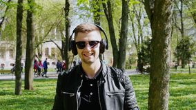 Το πορτρέτο κινηματογραφήσεων σε πρώτο πλάνο του ελκυστικού ατόμου βάζει στα ακουστικά και το άκουσμα στη μουσική φιλμ μικρού μήκους
