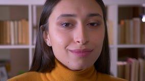 Το πορτρέτο κινηματογραφήσεων σε πρώτο πλάνο του νέου και όμορφου δασκάλου brunette χαμογελά ευτυχώς στη κάμερα στη βιβλιοθήκη φιλμ μικρού μήκους
