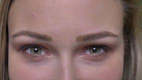 Το πορτρέτο κινηματογραφήσεων σε πρώτο πλάνο του νέου ξανθού προτύπου μόδας ανοίγει τα μάτια και τα ρολόγια της σοβαρά στη κάμερα απόθεμα βίντεο