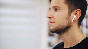 Το πορτρέτο κινηματογραφήσεων σε πρώτο πλάνο του νεαρού άνδρα με τα ακουστικά ακούει τη μουσική στα airpods και το χαμόγελο απόθεμα βίντεο
