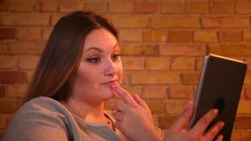 Το πορτρέτο κινηματογραφήσεων σε πρώτο πλάνο του υπέρβαρου θηλυκού freelancer κάθεται στον καναπέ που λειτουργεί με την ταμπλέτα  απόθεμα βίντεο