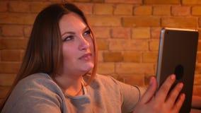 Το πορτρέτο κινηματογραφήσεων σε πρώτο πλάνο του υπέρβαρου χαρούμενου θηλυκού προτύπου κάθεται στον καναπέ που μιλά στο videochat απόθεμα βίντεο