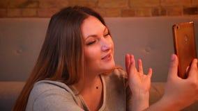 Το πορτρέτο κινηματογραφήσεων σε πρώτο πλάνο του υπέρβαρου χαρούμενου θηλυκού προτύπου που μιλά ενεργά να έχε το βίντεο καλεί την φιλμ μικρού μήκους