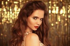 Το πορτρέτο κοριτσιών μόδας ομορφιάς που απομονώνεται στα χρυσά Χριστούγεννα ακτινοβολεί υπόβαθρο φω'των bokeh Γοητεία makeup Χρυ στοκ εικόνες