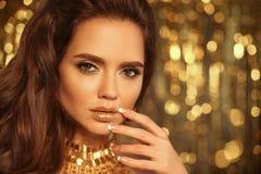 Το πορτρέτο κοριτσιών ομορφιάς μόδας που απομονώνεται στα χρυσά φω'τα Χριστουγέννων ακτινοβολεί bokeh υπόβαθρο Γοητεία makeup Χρυ στοκ φωτογραφίες
