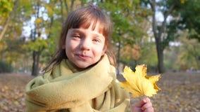 Το πορτρέτο λίγου χαμογελώντας κοριτσιού με το κίτρινο φύλλο σε την παραδίδει το πάρκο φθινοπώρου απόθεμα βίντεο