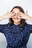 Το πορτρέτο μιας γελώντας γυναίκας που κλείνει τα μάτια της με παραδίδει το άσπρο υπόβαθρο , στοκ εικόνες