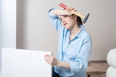 Το πορτρέτο μιας κουρασμένης γυναίκας brunette με ένα σφυρί στα χέρια της, σκουπίζει το μέτωπό της με τον ιδρώτα, συνέλευση επίπλ στοκ φωτογραφία με δικαίωμα ελεύθερης χρήσης