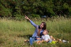 Το πορτρέτο μιας μητέρας με έναν νέο γιο τρώει σε ένα πικ-νίκ στο δάσος στοκ φωτογραφία