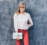 Το πορτρέτο μιας νέας γυναίκας έντυσε σε μια μπλούζα, κόκκινο παντελόνι Chino, ένα τυρκουάζ τσαντών στον ώμο της Τοποθέτηση δίπλα Στοκ Εικόνα