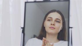 Το πορτρέτο μιας νέας γυναίκας με την κρέμα ή το καλλυντικό καλύπτει στο πρόσωπό της απόθεμα βίντεο