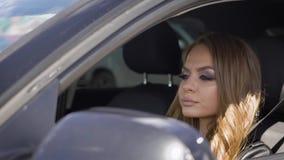 Το πορτρέτο μιας νέας και όμορφης γυναίκας με μια φωτεινή σύνθεση στα μάτια της που κάθεται στο όχημα, η κυρία είναι στο α απόθεμα βίντεο