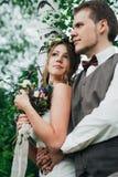 Το πορτρέτο μιας νύφης και ο νεόνυμφος αγκαλιάζουν στο δάσος φύλλων υποβάθρου Στοκ Φωτογραφία