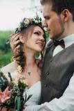 Το πορτρέτο μιας νύφης και ο νεόνυμφος αγκαλιάζουν στο δάσος φύλλων υποβάθρου Στοκ Φωτογραφίες