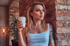 Το πορτρέτο μιας ξανθής γυναίκας hipster κρατά το φλιτζάνι του καφέ κλίνοντας ενάντια σε έναν τουβλότοιχο σε ένα δωμάτιο με το εσ Στοκ εικόνα με δικαίωμα ελεύθερης χρήσης