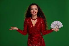 Το πορτρέτο μιας σγουρής γυναίκας brunette σε ένα ακτινοβολημένο φόρεμα, που κρατά τον ανεμιστήρα δίπλωσε τα χρήματα casino στοκ εικόνα με δικαίωμα ελεύθερης χρήσης