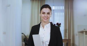 Το πορτρέτο μιας χαμογελώντας επιχειρηματία σε ένα περιστασιακό κοστούμι που φαίνεται ευθύ στη κάμερα, έχει ένα μεγάλο άσπρο χαμό φιλμ μικρού μήκους