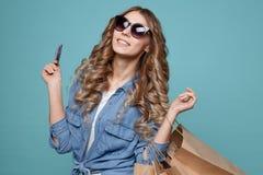 Το πορτρέτο μιας χαρωπής όμορφης φθοράς κοριτσιών ντύνει και γυαλιά ηλίου κρατώντας τις τσάντες αγορών και παρουσίαση πιστωτικής  στοκ φωτογραφίες με δικαίωμα ελεύθερης χρήσης