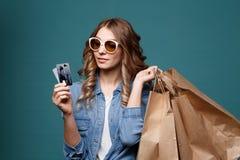 Το πορτρέτο μιας χαρωπής όμορφης φθοράς κοριτσιών ντύνει και γυαλιά ηλίου κρατώντας τις τσάντες αγορών και παρουσίαση πιστωτικής  στοκ φωτογραφίες