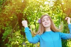 Το πορτρέτο μιας όμορφης νέας γυναίκας με ένα στεφάνι σταθμεύει την άνοιξη Στοκ Φωτογραφία