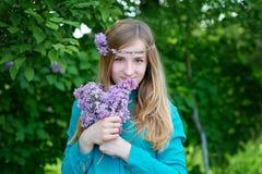 Το πορτρέτο μιας όμορφης νέας γυναίκας με ένα στεφάνι σταθμεύει την άνοιξη Στοκ Εικόνες
