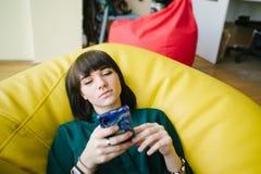 Το πορτρέτο μιας όμορφης νέας συνεδρίασης σπουδαστών σε μια τσάντα καρεκλών και χρησιμοποιεί το τηλέφωνο πασπαλίζοντας στοκ εικόνα